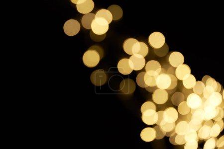 Photo pour Beau bokeh de golden défocalisé brillant sur fond noir - image libre de droit