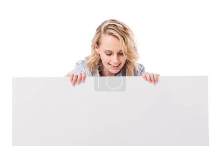 smiling attractive woman looking at blank placard isolated on white