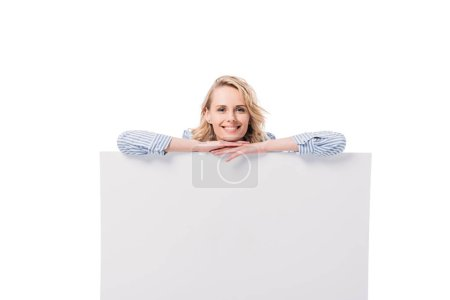 Photo for Smiling attractive woman leaning on blank placard isolated on white - Royalty Free Image