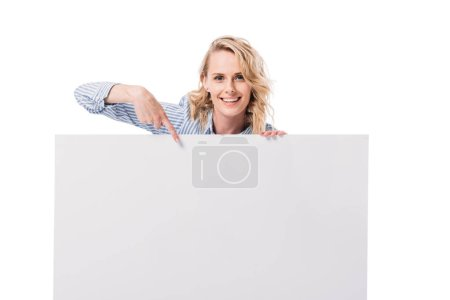 smiling attractive woman pointing on blank placard isolated on white