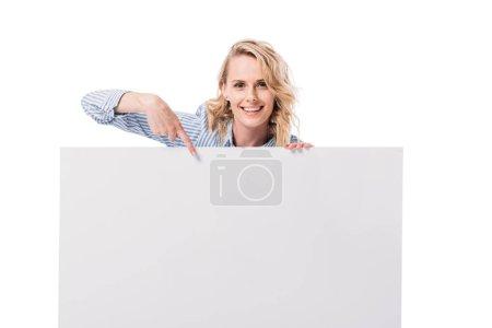 Photo pour Souriant attrayant femme pointant sur plaque vierge isolé sur blanc - image libre de droit
