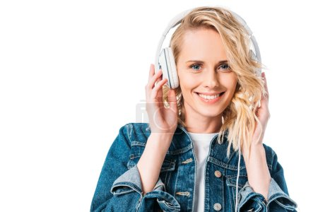 beautiful woman listening to music with headphones and looking at camera isolated on white