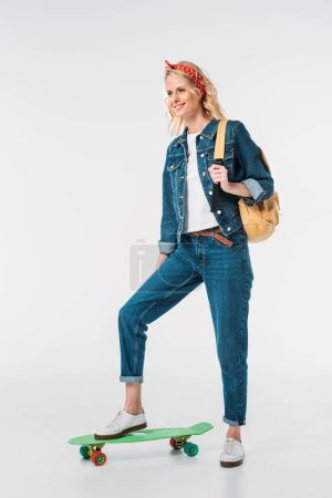 attractive woman putting leg on skateboard isolated on white