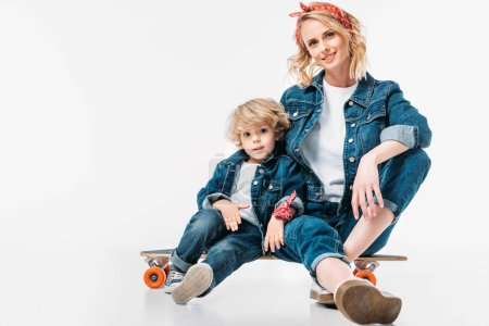 mother and son sitting on skateboard and looking at camera on white