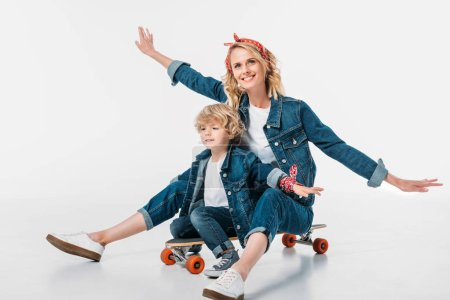 happy mother and son sitting on skateboard and pretending flying on white