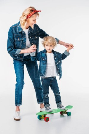 mother helping son standing on skateboard on white