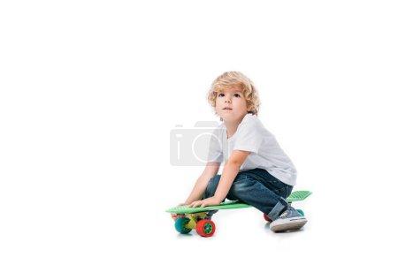 Photo pour Adorable garçon assis sur skateboard isolé sur blanc - image libre de droit