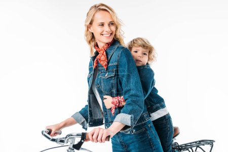 smiling mother and son riding bicycle isolated on white