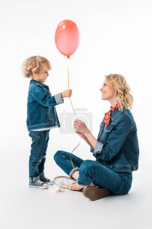 side view of son presenting red balloon to mother on white