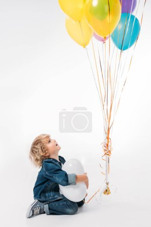 adorable boy looking at bundle of balloons on white