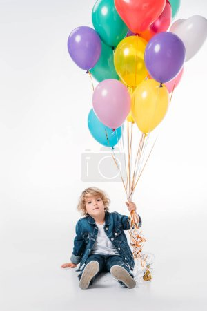 adorable boy sitting and holding bundle of balloons on white