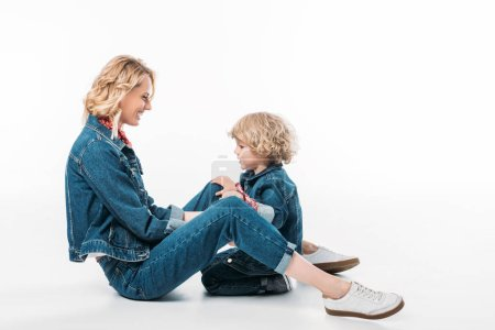 side view of smiling mother and son sitting on floor on white