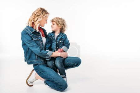 happy mother and son squatting and looking at each other isolated on white