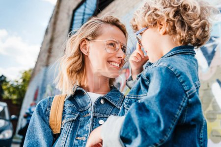 Photo for Happy mother and son looking at each other on street - Royalty Free Image