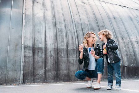 happy mother and son blowing soap bubbles on street