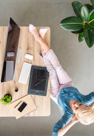 Foto de Vista aérea de teletrabajador mujer elegante sentado con las piernas en la mesa con ordenador, teléfono inteligente y tableta gráfica en casa - Imagen libre de derechos
