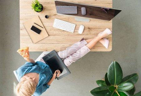 Foto de Vista superior de estilo freelance mujer comiendo pizza y con tableta gráfica con las piernas sobre la mesa en casa - Imagen libre de derechos