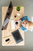 elevated view of smiling female freelancer looking at camera and holding cup of coffee at table with graphic tablet, smartphone and computer at home office