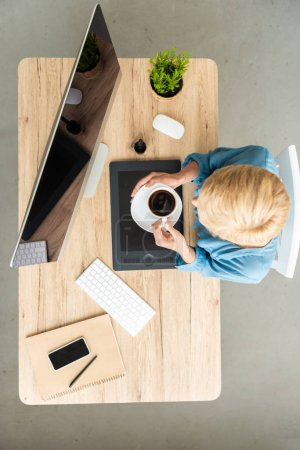 Foto de Vista aérea de freelance mujer sosteniendo la taza de café a la mesa digitalizadora, smartphone y ordenador en la oficina en casa - Imagen libre de derechos