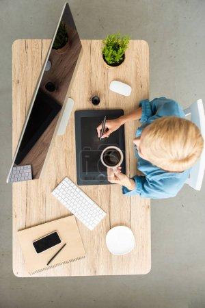 Foto de Vista aérea de café bebe mujer freelance trabajando en tableta gráfica en mesa con smartphone y computadora en casa oficina - Imagen libre de derechos