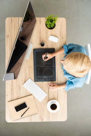 Photo for Top view of female freelancer working on graphic tablet at table with cup of coffee, smartphone and computer at home office - Royalty Free Image