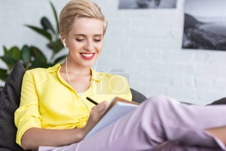 smiling young woman in earphones writing in textbook on sofa at home