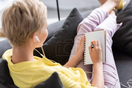 rear view of young woman in earphones writing in textbook on sofa at home