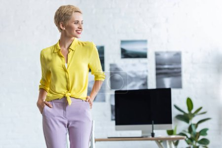 smiling businesswoman with hands in pockets looking away at office