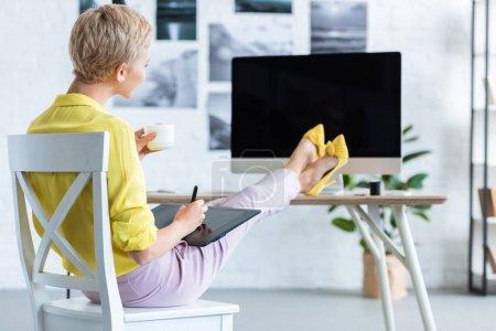 Foto de Enfoque selectivo de independiente mujer bebiendo café y usando tableta gráfica en mesa con ordenador en la oficina en casa - Imagen libre de derechos
