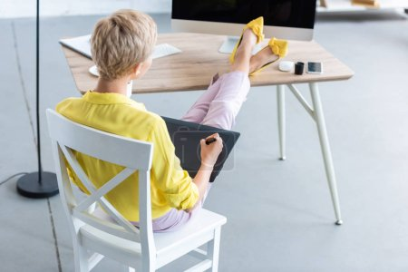 rear view of female freelancer working on graphic tablet at table with computer at home office