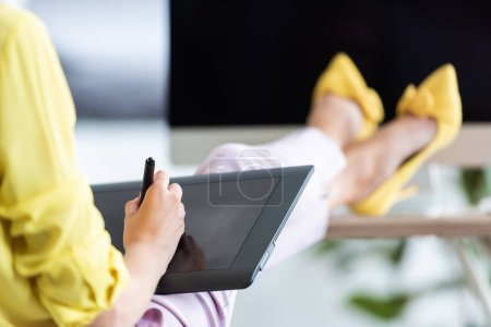 cropped image of female freelancer using graphic tablet at table with computer at home office