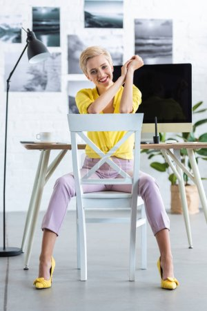 stylish businesswoman sitting on chair and looking at camera at office
