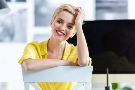 smiling businesswoman sitting on chair and looking at camera at office
