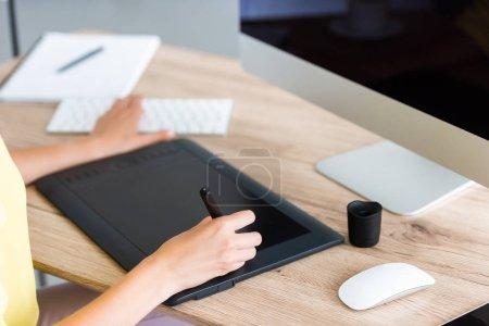 Foto de Imagen recortada de mujer independiente en tableta gráfica en mesa con ordenador - Imagen libre de derechos