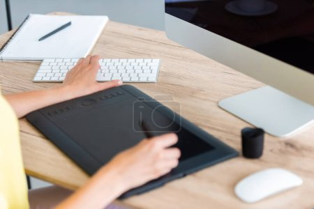 cropped image of female freelancer drawing on graphic tablet at table with computer