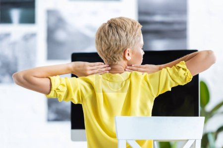 rear view of businesswoman doing stretch while sitting at table with computer at home