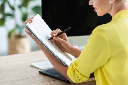 cropped image of smiling female freelancer writing in textbook at table with graphic tablet and computer