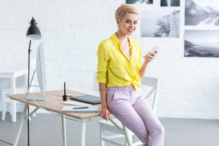 smiling female freelancer using smartphone near table with graphic tablet and computer at home office