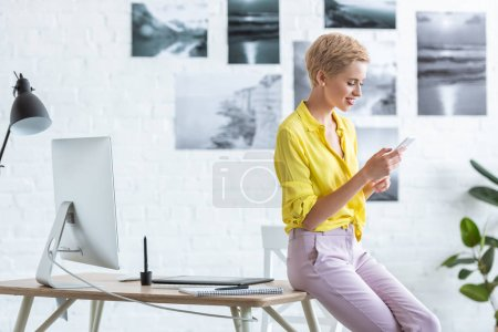 Photo for Side view of smiling female freelancer using smartphone near table with graphic tablet and computer at home office - Royalty Free Image