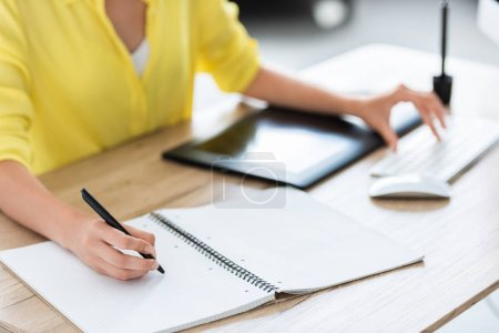 cropped image of female freelancer writing in textbook and working on computer at home office