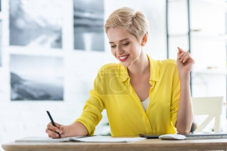 smiling female freelancer writing in textbook at table with graphic tablet and computer at home office