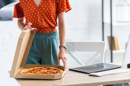 Photo for Cropped image of female freelancer opening pizza box at table with graphic tablet and computer - Royalty Free Image