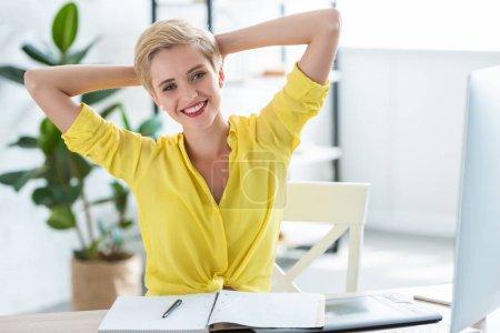 Photo pour Portrait de l'heureuse femme freelance avec larges bras assis à table avec manuel, tablette graphique et informatique - image libre de droit