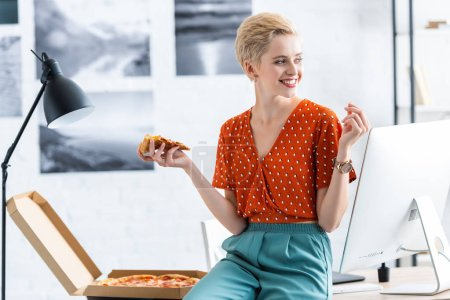 smiling female freelancer sitting on table and eating pizza at home office