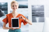 smiling woman presenting digital tablet with blank screen