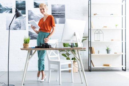 Photo pour Photographe élégant en utilisant une tablette numérique près de table avec caméra photo et l'ordinateur dans le Bureau à domicile - image libre de droit