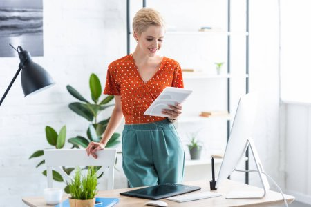 female freelancer using digital tablet near table with computer in home office