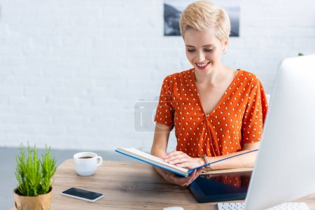 smiling female freelancer reading book at table with graphic tablet and computer in home office