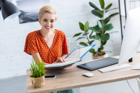 female freelancer holding book at table with graphic tablet and computer in home office