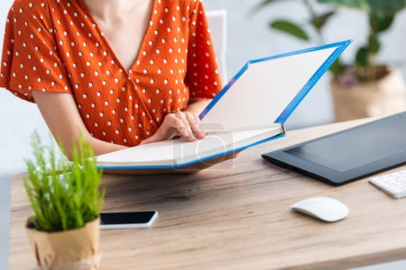 Photo pour Image recadrée de livre de lecture féminine pigiste à table avec tablette graphique, smartphone et ordinateur de bureau à domicile - image libre de droit